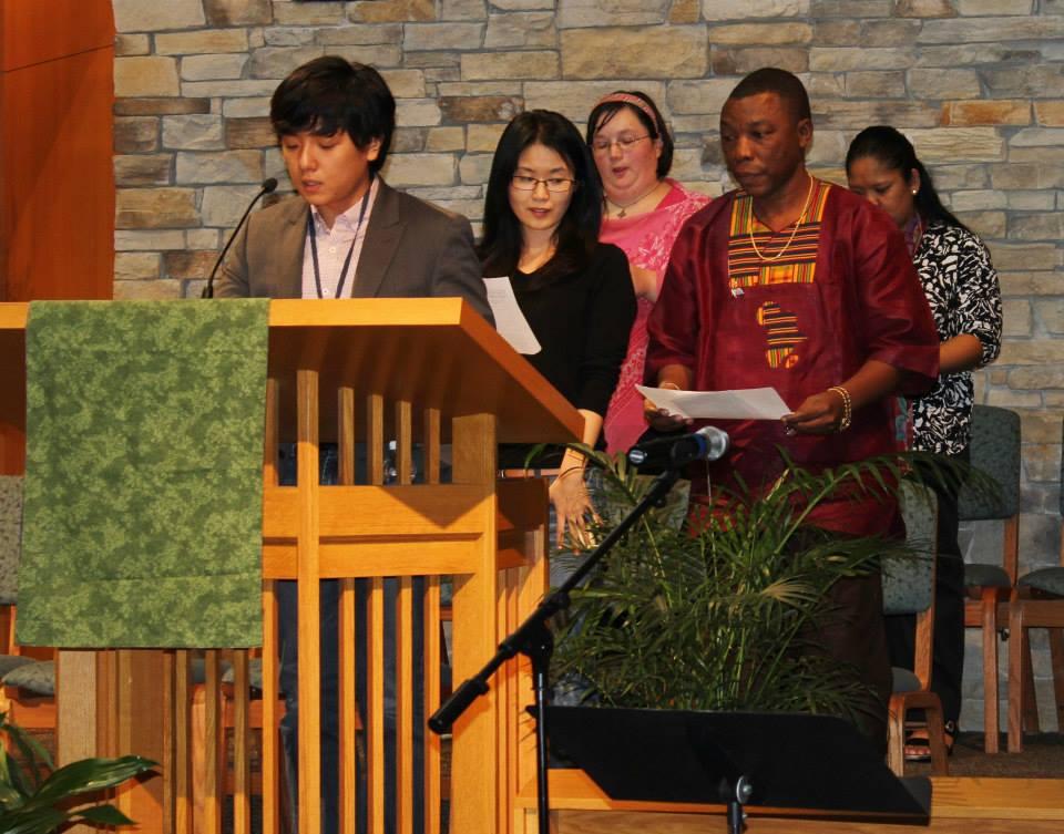 A group of international theological degree students speaking at a podium.
