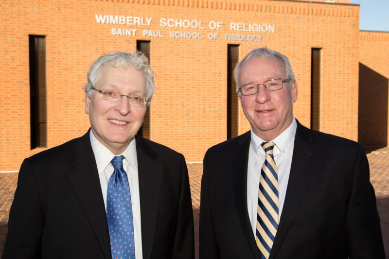 Oklahoma City University President Robert Henry and Rev. Neil Blair, President of Saint Paul School of Theology pictured side-by-side in front of Wimberly School of Religion building.