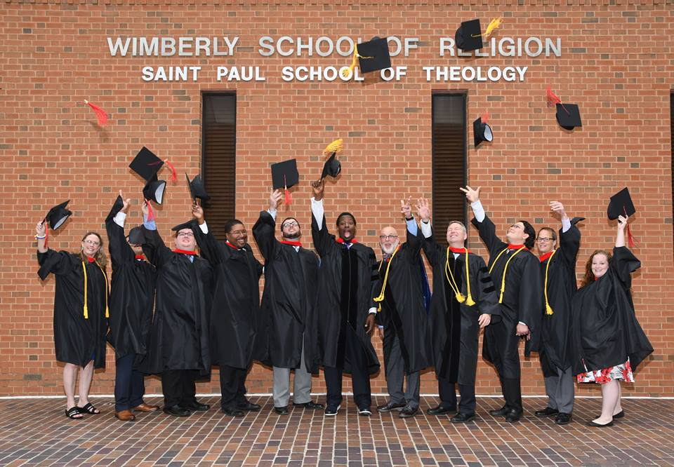 Saint Paul School of Theology Oklahoma Campus graduates throwing caps at commencement.