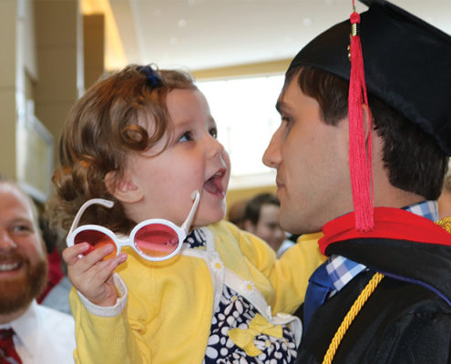 Photo of father holding his daughter after graduating with the help of our hybrid and online theology degree.