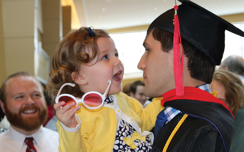 Photo of father holding his daughter after graduating with the help of hybrid and online theology degree.