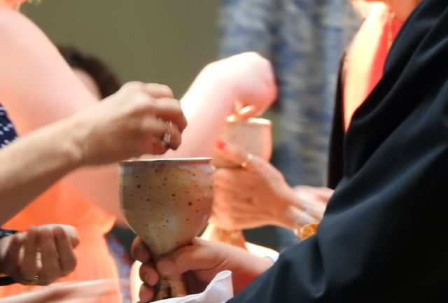 woman offers parishoner wine cup during worship
