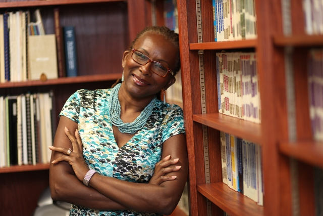 Dr. Angela Simms leans against a bookshelf at Saint Paul School of Theology.
