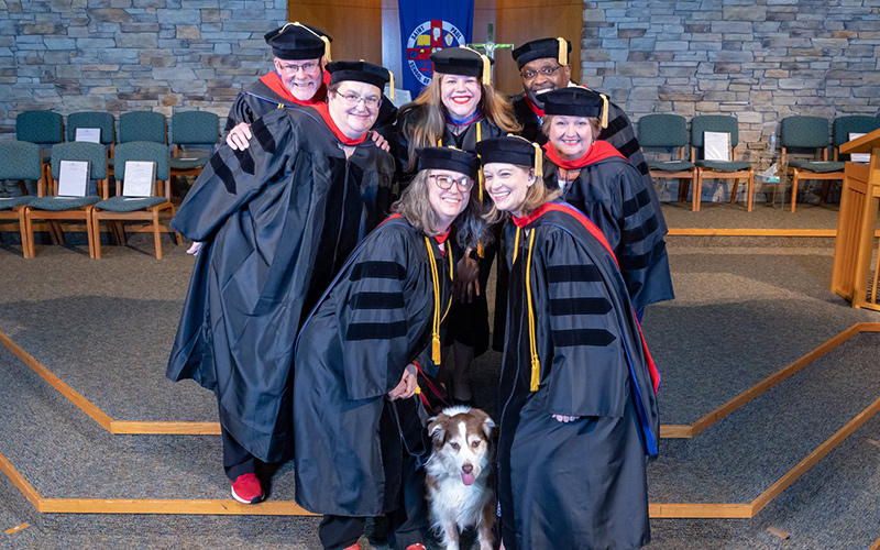 Male and female Saint Paul School of Theology graduates pose in gowns and smile with a dog sitting at their feet.