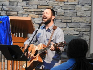 Music minister playing guitar in worship