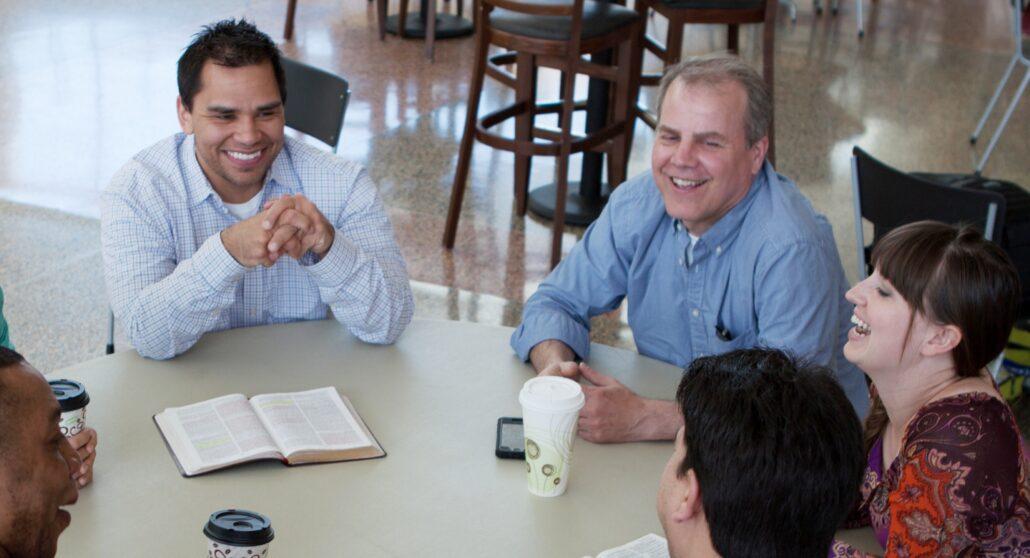 Seminary students visiting at a table