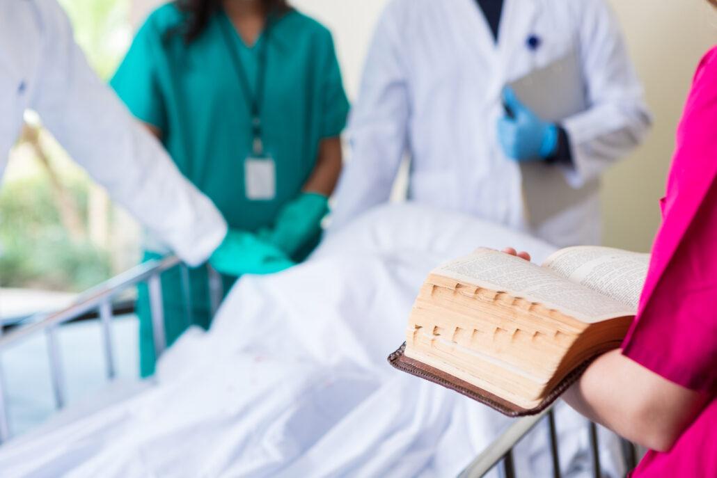 Chaplain reading scripture in patient room